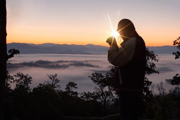 キリスト教の男の手の祈り、精神性および宗教、神に祈る人のシルエット