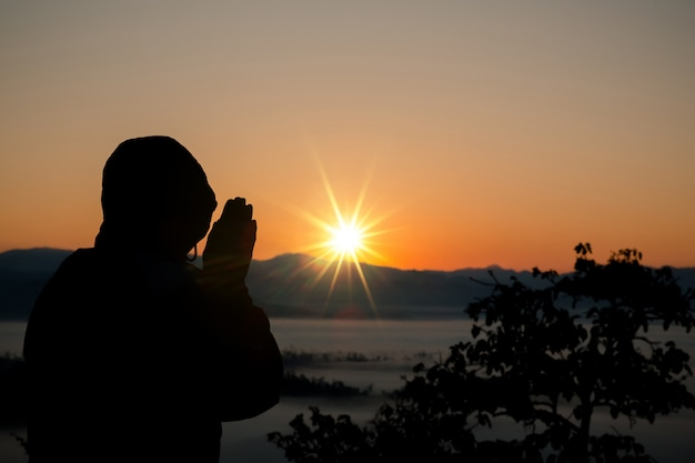 祈っているキリスト教の男のシルエット