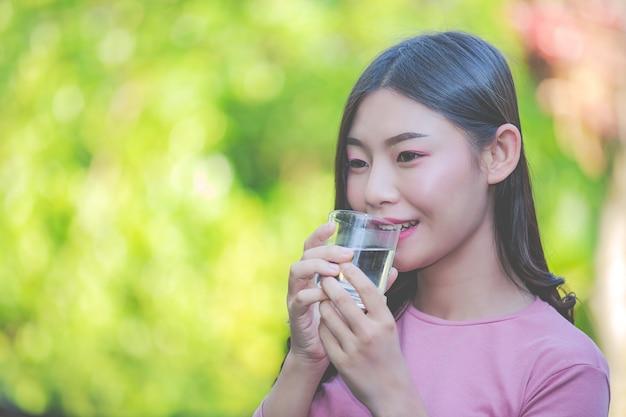 美しい女性はコップ一杯の水からきれいな水を飲む