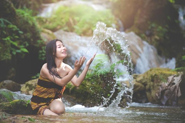 自然の滝で幸せな入浴女性