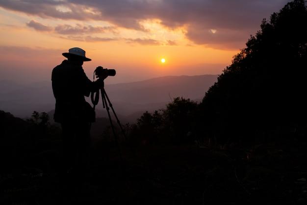 山の夕日を撮影する写真家のシルエット