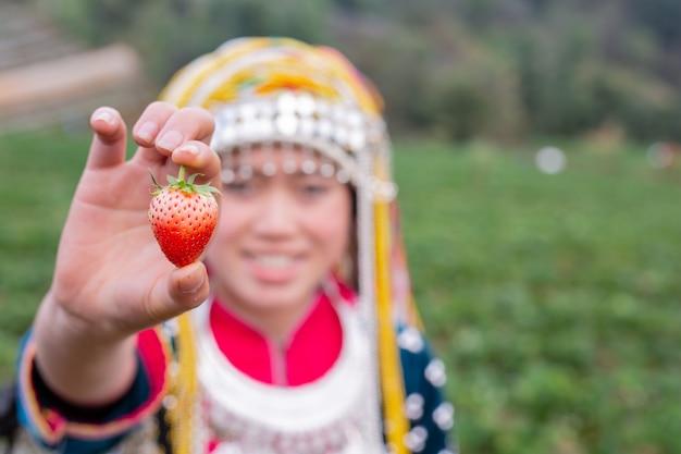 部族の女の子がイチゴを集めています