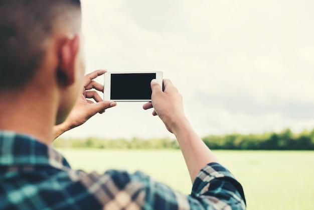 Человек, принимая фотографии с его телефона