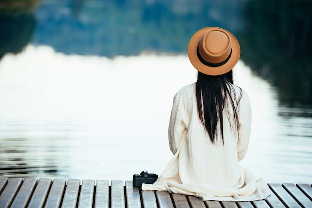 ウォーターフロントのいかだに座っている孤独な女性