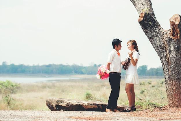 Пара в любви с игрой на гитаре на природе