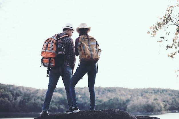 山を背景に旅行カップル