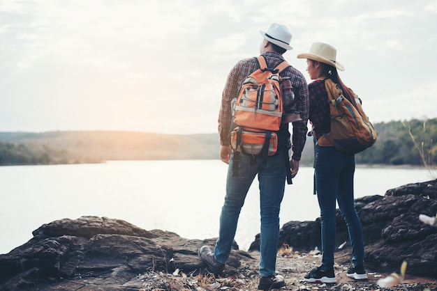 山の上のバックパックと観光客のカップル