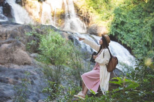 女性観光客は自然の上を歩いています。