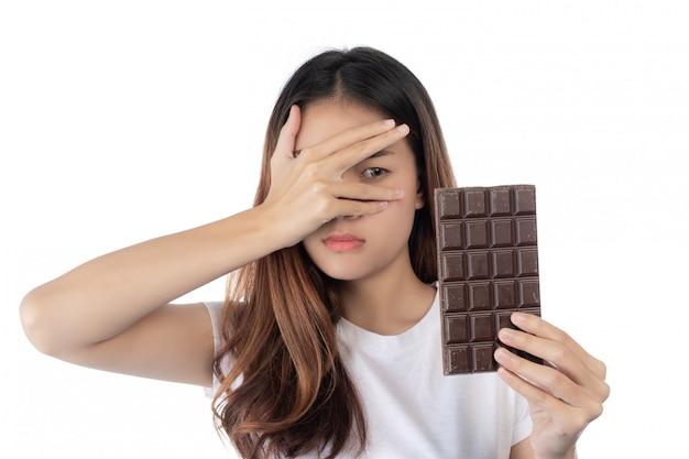 Женщины против шоколада, изолированные на белом фоне.