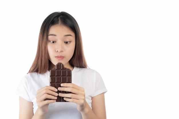 白い背景で隔離の手チョコレートを持って幸せな笑顔を持つ美しい女性。