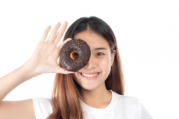 白い背景で隔離の手のドーナツを持って幸せな笑顔を持つ美しい女性。