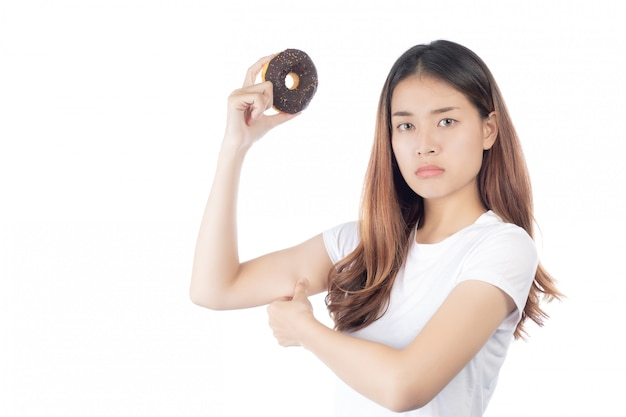 ドーナツを手で押し、幸せな笑顔で美しいアジアの女性