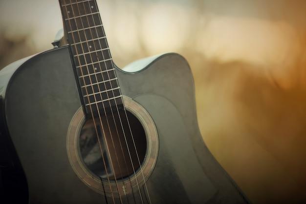 夕日の風景の背景に牧草地のアコースティックギター