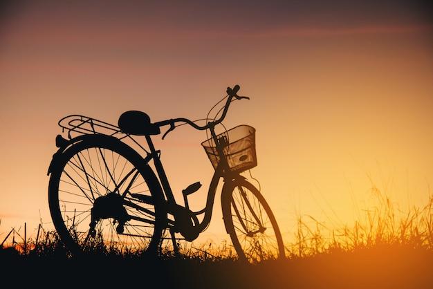 日没時のビンテージバイクのシルエット