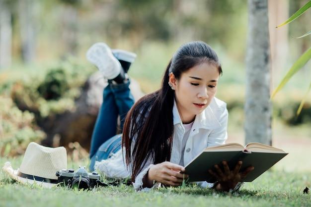 Красивая девушка в осеннем лесу читает книгу