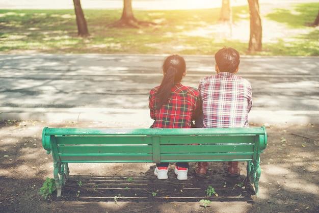 でベンチに一緒に座って恋に若い十代のカップル