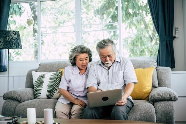 ラップトップコンピューターと話している年配のカップル
