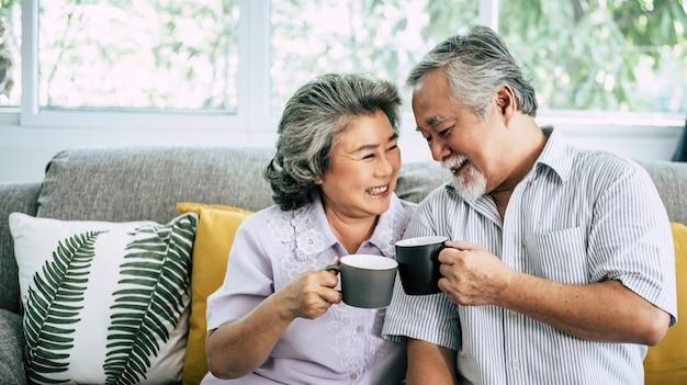 Пожилая пара говорить вместе и пить кофе или молоко