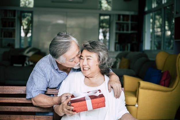 彼の妻にギフト用の箱を与える驚きをする笑顔のシニア夫