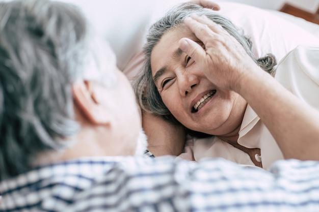 Пожилые супружеские пары, лежа в постели вместе