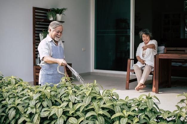 Пожилая пара поливает цветок в домашнем саду