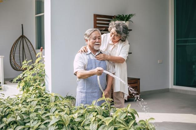老夫婦の家の庭で花に水をまく