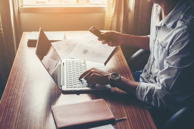 オフィスのデスクでノートパソコンと携帯電話を使用して、ビジネスマンの手。