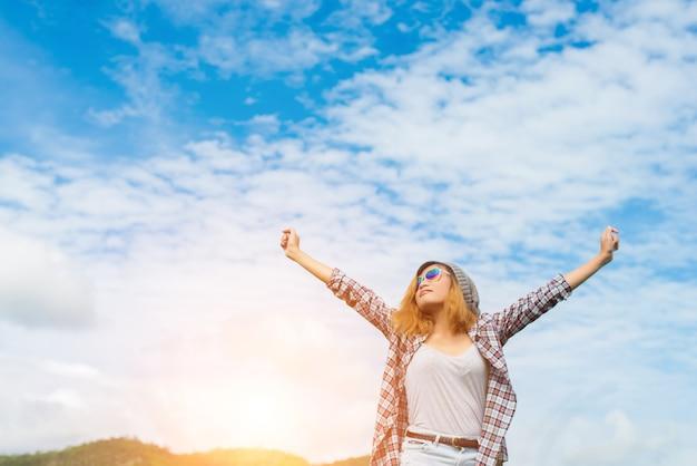 背後にある自然の中で自由と人生を楽しんで若い美しい女性