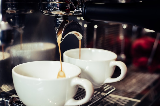 バリスタはカフェでコーヒーマシンを使用しています。