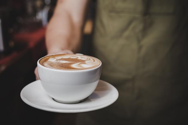 Бариста обрабатывает горячее кафе латте.