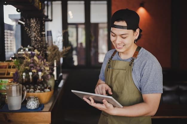 アジア人男性バリスタコーヒーカフェで顧客からの注文を確認するためのタブレットを保持しています。