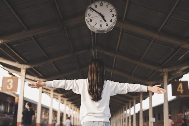 女性は駅で旅行している間幸せです。観光の概念