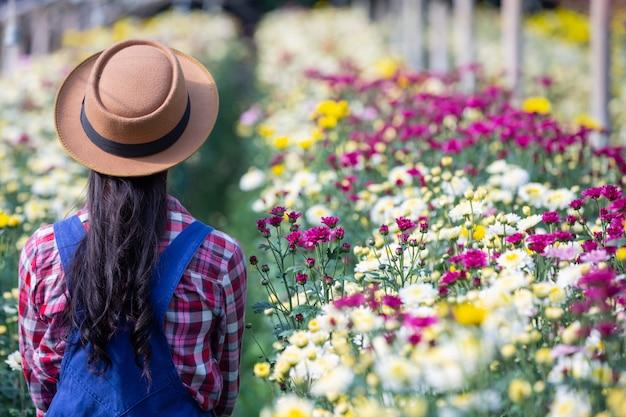 少女は庭の花を賞賛しています。