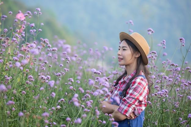 若い農夫は庭の花を賞賛します。