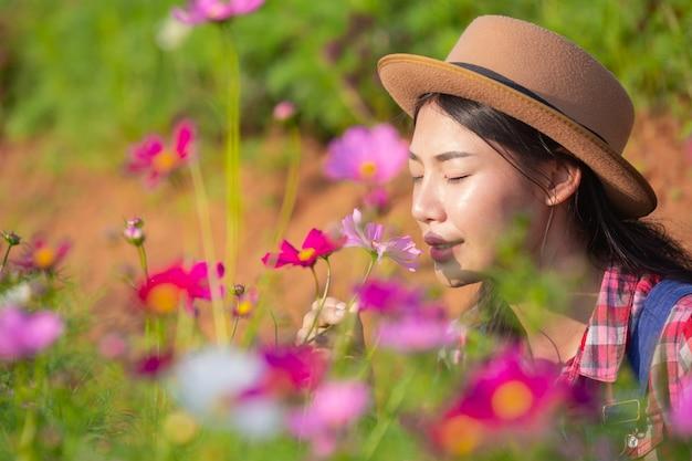 女性農家は花畑を賞賛しています。