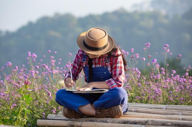 農家の女性は花畑でメモを取っています。