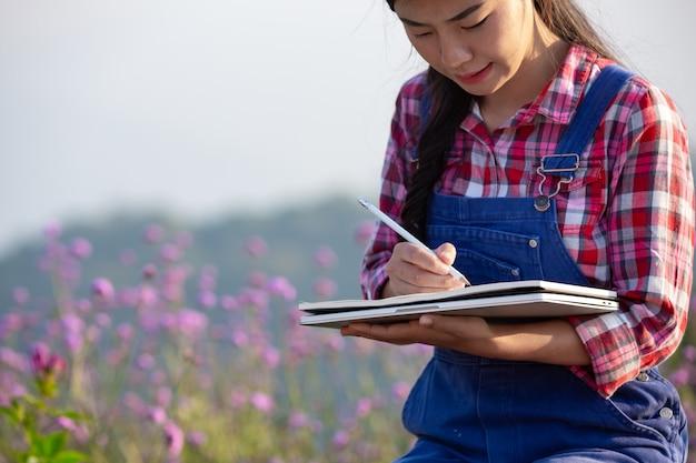 Фермеры-женщины делают записи в цветочном саду.