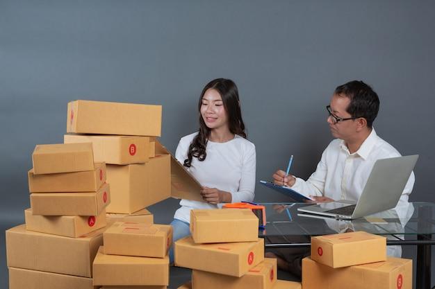 Мужчины и женщины помогают упаковывать коробки.