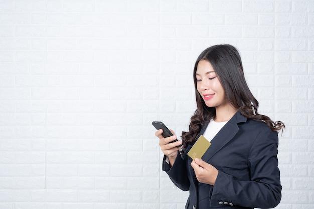 別の現金カード、白いレンガの壁を保持している女性実業家手話でジェスチャーをした。