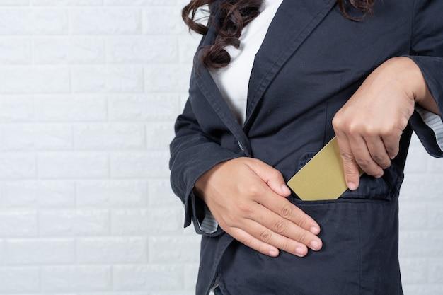 Деловая женщина, держащая отдельную кредитную карту, белая кирпичная стена сделанные жесты с языком жестов.