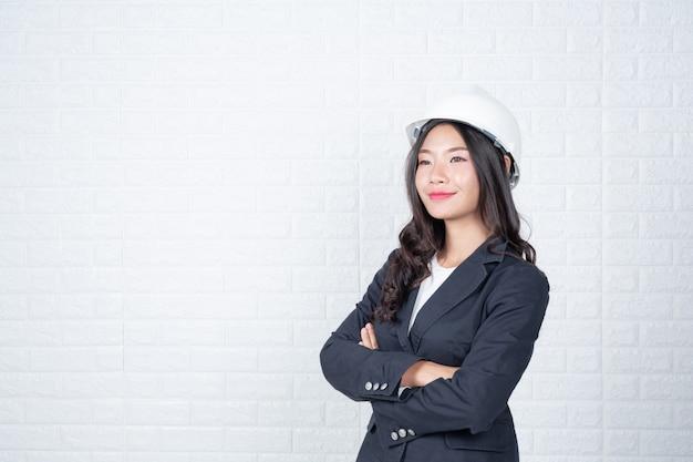 帽子をかぶって工学の女性、白いレンガの壁を分離した手話でジェスチャーをしました。
