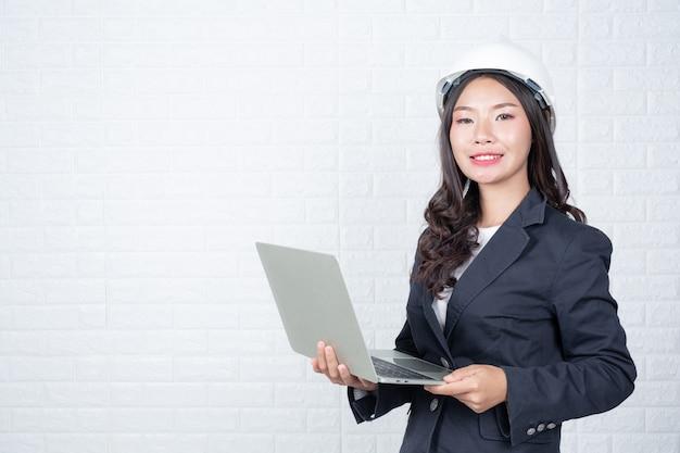 Инженерная женщина, держащая отдельную тетрадь, белая кирпичная стена.