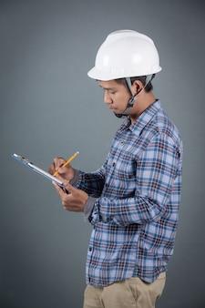 Инженер держа светокопии и читая примечания на доске сзажимом для бумаги пока стоящ на серой предпосылке.
