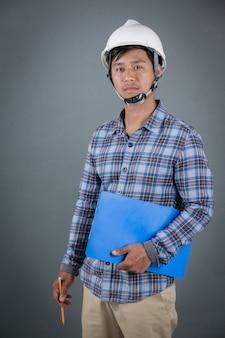 エンジニアの青写真を押しながら灰色の背景上に立っている間クリップボードにメモを読む。