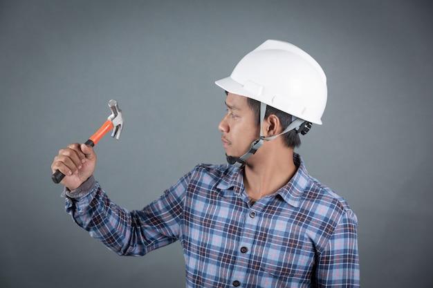 Строитель держит молоток на сером фоне.
