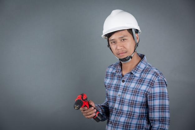 Строитель держит дрель на сером фоне