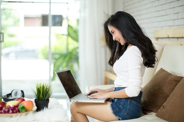 自宅でラップトップコンピューターを使用して若い美しい女性。