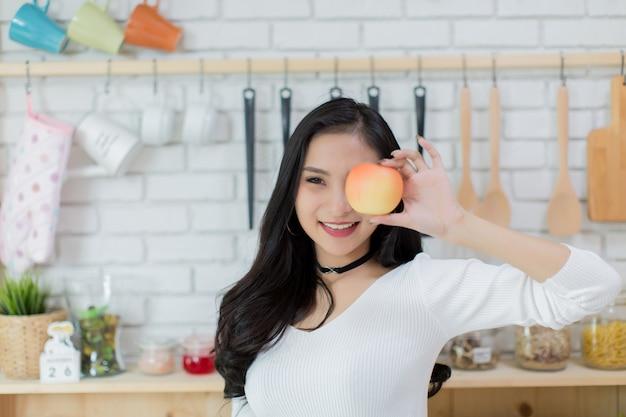 ケーキとアップルの間の選択をする美しい若い女性