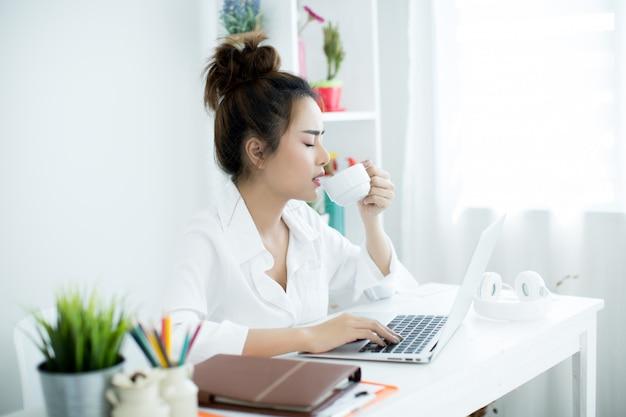 Красивая молодая женщина работает на своем ноутбуке в своей комнате.