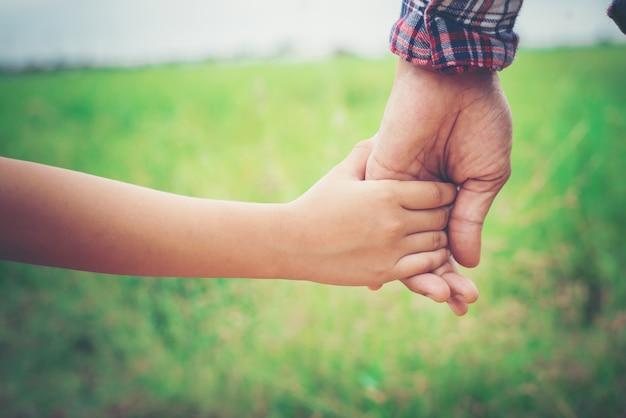 Крупным планом отец держит свою дочь за руку, так сладко, семейный ти